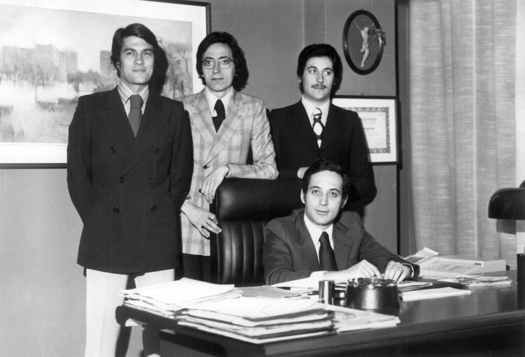 Alla scrivania Paolo Capogrossi con i due fratelli Massimo (in piedi a destra) e Fabio (in piedi al centro) ed un collaboratore